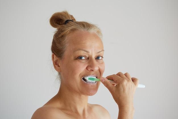 Mulher madura escovando os dentes com escova de dentes como rotina matinal saudável