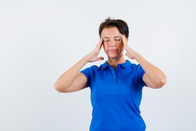 Mulher madura esfregando as têmporas em uma camiseta azul e parecendo relaxada. vista frontal.