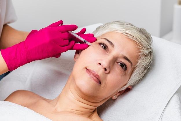 Mulher madura está recebendo injeções faciais rejuvenescedoras. ela está deitada calmamente na clínica. a esteticista especialista está injetando botox nas rugas das mulheres.