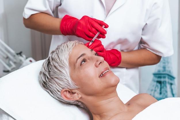 Mulher madura está recebendo injeções rejuvenescedoras de botulina facial.