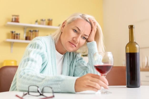 Mulher madura estressada bebendo vinho em casa