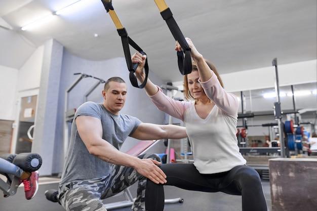 Mulher madura, exercitando-se no ginásio usando loops de tiras de fitness