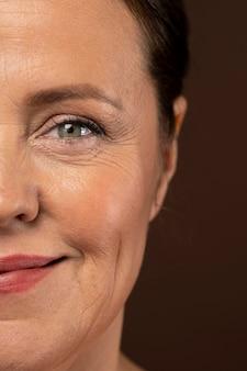 Mulher madura exibindo metade do rosto com maquiagem