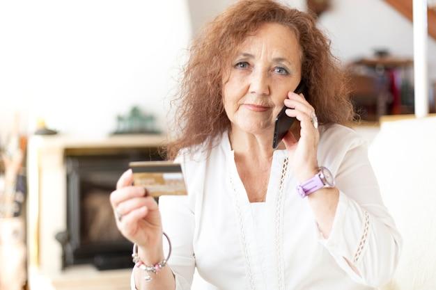 Mulher madura falando ao telefone de sua casa, segurando um cartão de crédito na mão.