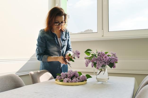 Mulher madura fazendo buquê de ramos lilás