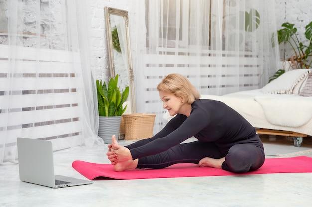 Mulher madura fazendo esportes em casa em uma esteira, conceito de estilo de vida saudável