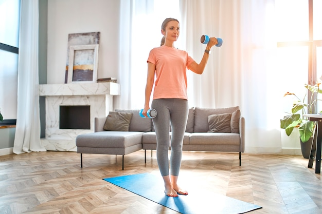 Mulher madura fazendo exercícios com halteres em casa.
