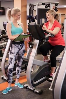 Mulher madura fazendo exercícios com o treinador