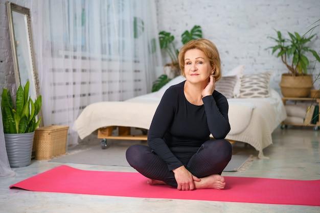 Mulher madura fazendo yoga sentado no tapete em casa, conceito de estilo de vida saudável, sentado em casa