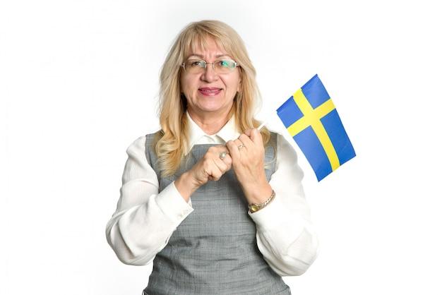 Mulher madura feliz com a bandeira da suécia em pé sobre um fundo branco.