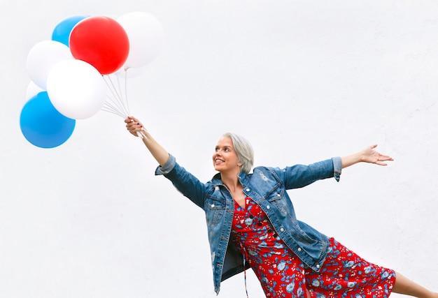 Mulher madura feliz com balões brancos, vermelhos e azuis no fundo da parede branca