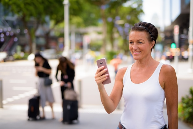 Mulher madura feliz e linda turista pensando enquanto usa o telefone nas ruas da cidade ao ar livre