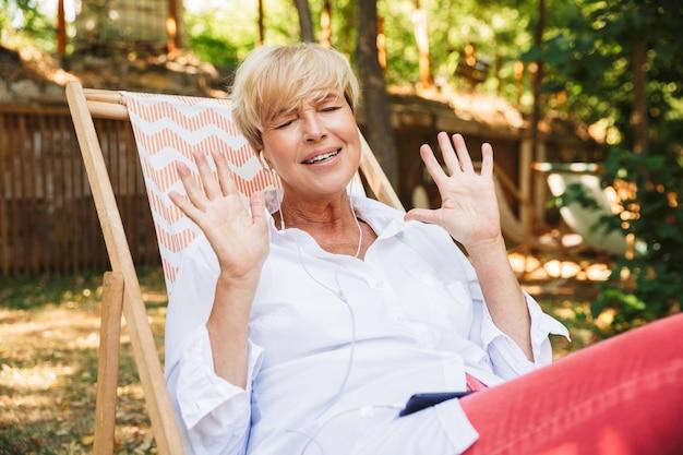 Mulher madura feliz ouvindo música com fones de ouvido