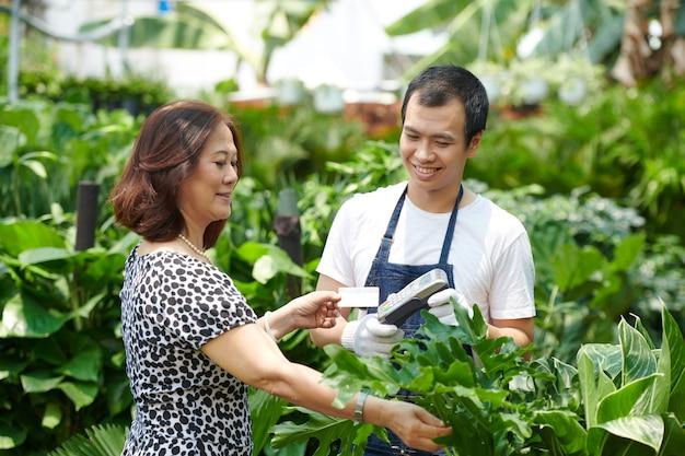 Mulher madura feliz pagando com cartão de crédito na compra de plantas para a casa dela no centro de jardinagem