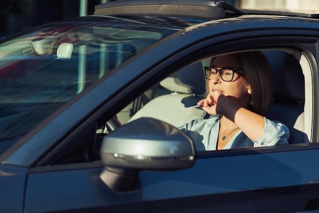 Mulher madura feliz usando óculos, segurando um cartão de plástico em branco na mão enquanto dirige seu carro moderno