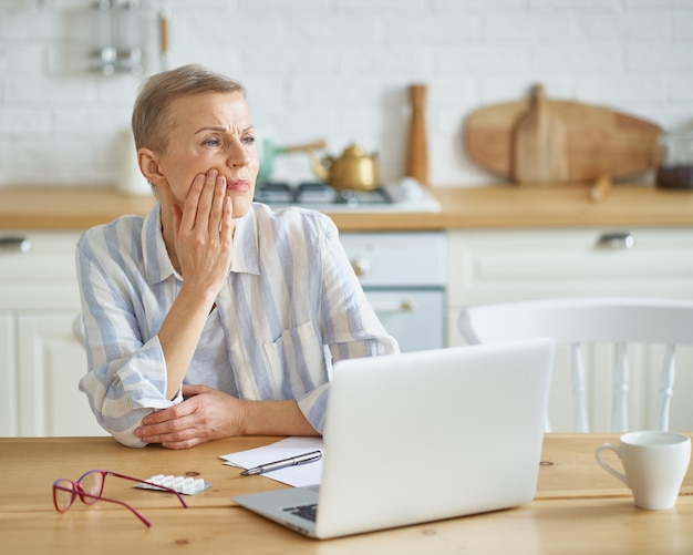 Mulher madura frustrada tocando sua bochecha e sofrendo de dor de dente enquanto está sentada na cozinha em