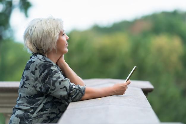 Mulher madura inclinada sobre um parapeito com o celular na mão, olhando para uma paisagem verde arborizada