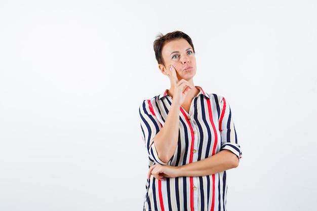 Mulher madura inclinando a bochecha no dedo indicador enquanto pensava em algo em uma camisa listrada e parecendo pensativa. vista frontal.