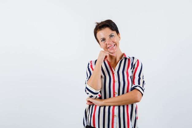 Mulher madura inclinando a bochecha por lado, segurando uma mão sob o cotovelo em uma camisa listrada e parecendo feliz, vista frontal.