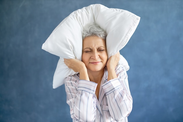 Mulher madura insatisfeita e irritada com cabelos grisalhos fazendo careta por ter uma noite sem dormir por causa da música alta