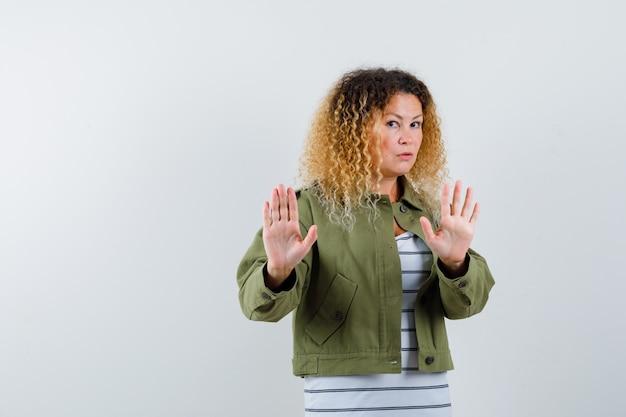 Mulher madura levantando as mãos para se defender em uma jaqueta verde, camiseta e parecendo assustada. vista frontal.