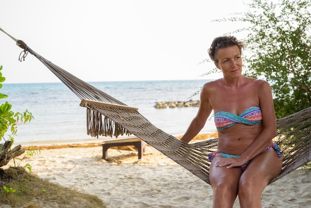 Mulher madura linda turista relaxando na praia