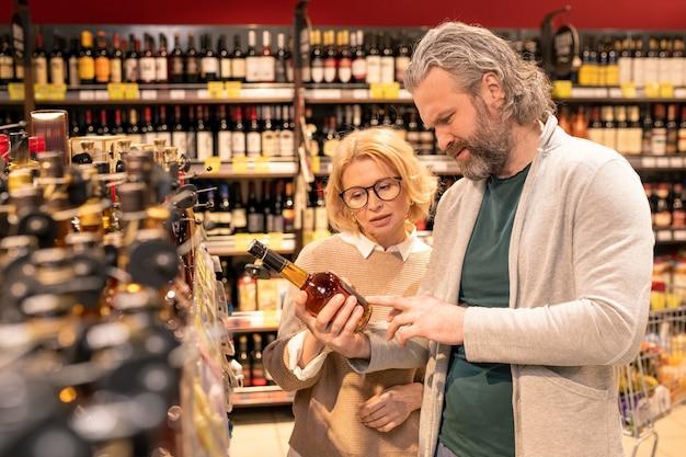 Mulher madura loira e bonita e o marido barbudo lendo informações no rótulo de uma garrafa de vinho ou conhaque no supermercado