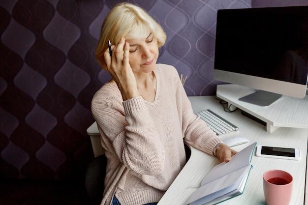 Mulher madura loira escrevendo em seu planejador enquanto trabalhava pelo computador em casa