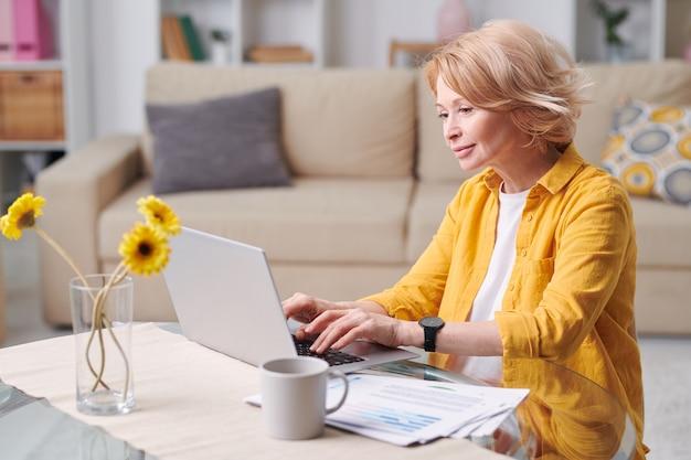 Mulher madura loira feliz em trajes casuais, sentada na mesa em frente ao laptop e trabalhando remotamente em casa durante a quarentena