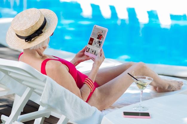 Mulher madura loira moderna que faz compras online usando um laptop enquanto toma banho de sol perto da piscina