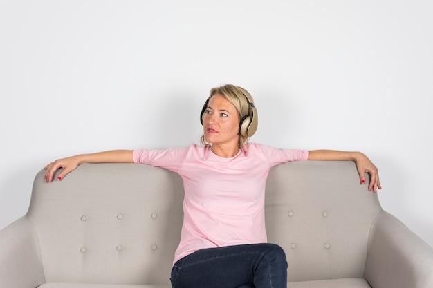 Mulher madura loira sentada no sofá, ouvindo música no fone de ouvido, olhando para longe