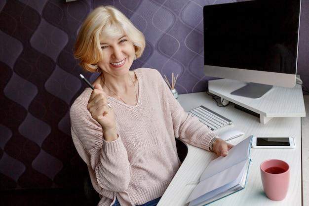 Mulher madura loira sorridente, escrevendo em seu planejador enquanto trabalhava pelo computador em casa