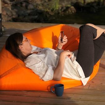 Mulher madura, lounging, uma cadeira, olhar, dela, telefone pilha, em, lago, de, a, madeiras, ontário