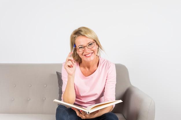 Mulher madura loura de sorriso que senta-se no sofá que guarda a pena e o livro contra o contexto branco