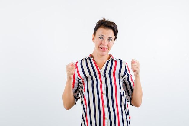 Mulher madura mostrando gesto de figo, mostrando a língua em uma blusa listrada e parecendo se divertir. vista frontal.