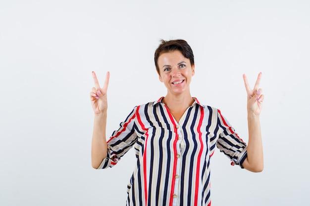 Mulher madura, mostrando o gesto de paz em camisa listrada e olhando feliz, vista frontal.