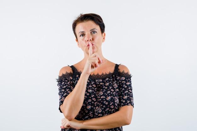 Mulher madura, mostrando o gesto de silêncio na blusa floral, saia preta e olhando séria, vista frontal.