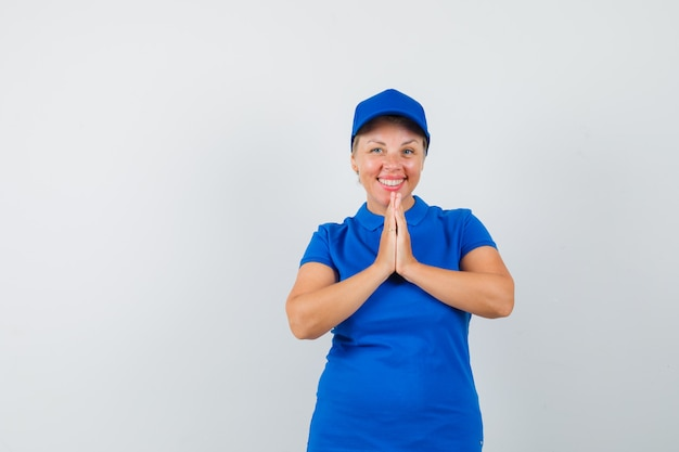 Mulher madura, mostrando o gesto namastê em camiseta azul e olhando feliz.