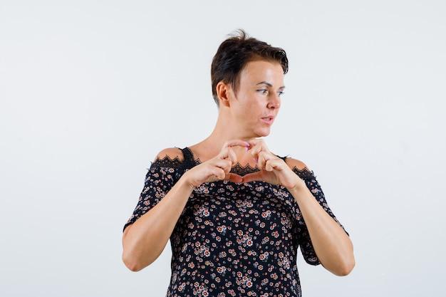Mulher madura, mostrando um gesto de amor com as mãos, olhando para longe na blusa floral, saia preta e parecendo pensativa. vista frontal.