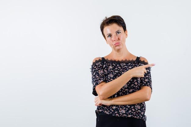 Mulher madura na blusa, apontando para o lado direito e parecendo confiante, vista frontal.