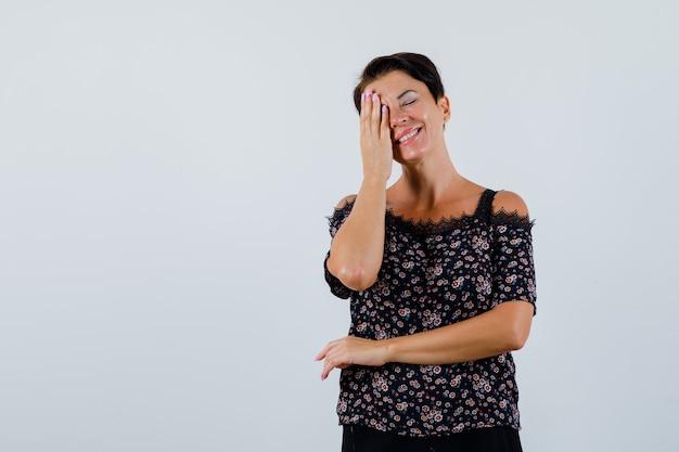 Mulher madura na blusa, cobrindo os olhos com a mão e parecendo feliz, vista frontal.