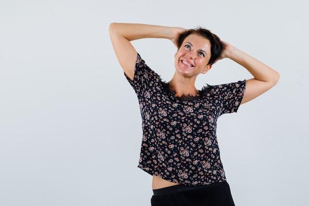 Mulher madura na blusa de mãos dadas atrás da cabeça enquanto olha para cima e olhando alegre, vista frontal.