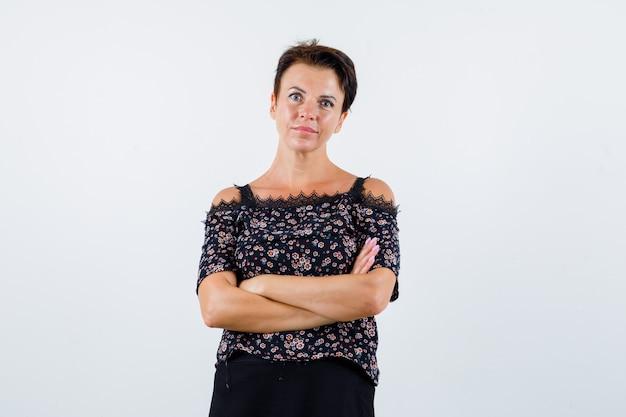 Mulher madura na blusa em pé com os braços cruzados e olhando confiante, vista frontal.