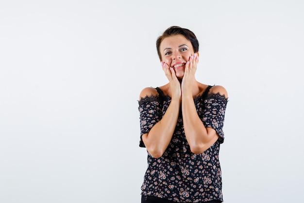Mulher madura na blusa floral, saia preta segurando as mãos nas bochechas, rindo e olhando alegre, vista frontal.