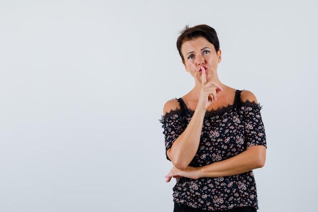 Mulher madura na blusa, mostrando o gesto de silêncio e olhando séria, vista frontal.