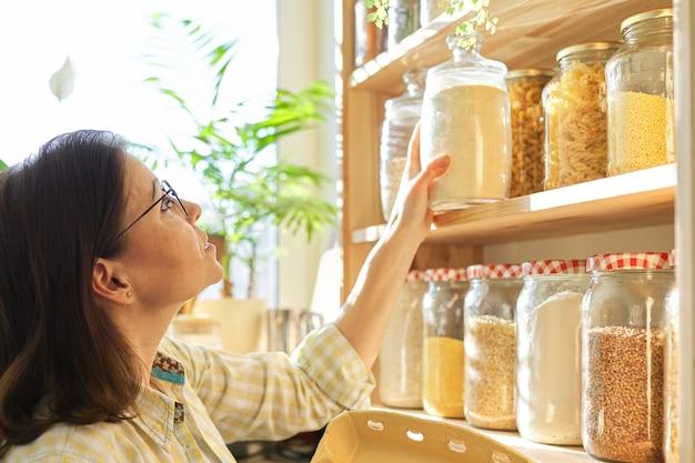 Mulher madura na despensa da cozinha com produtos
