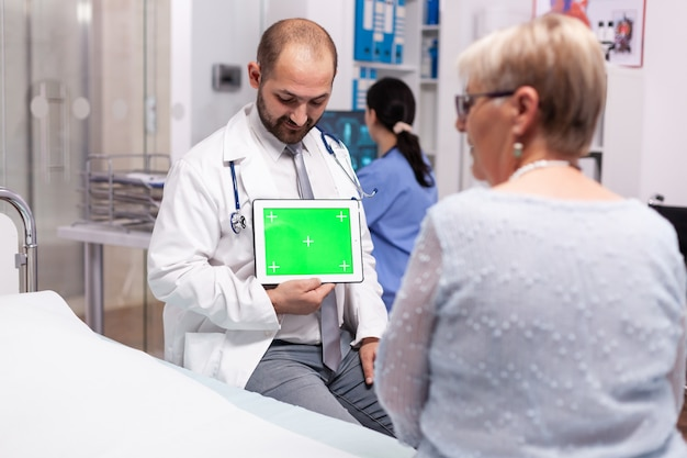 Mulher madura na sala de consulta do hospital, ouvindo médico com tela verde do tablet