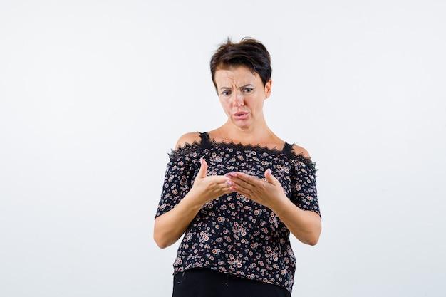 Mulher madura olhando para as palmas das mãos segurando algo em uma blusa floral, saia preta e parecendo surpresa. vista frontal.