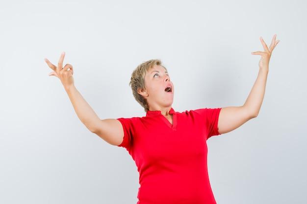 Mulher madura olhando para cima, levantando as mãos em uma camiseta vermelha e parecendo surpresa