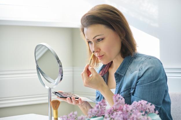 Mulher madura, olhando para o rosto no espelho, fazendo maquiagem